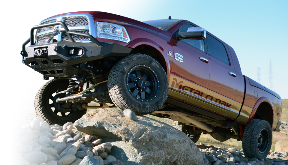 Red Dodge Ram with suspension on rocks