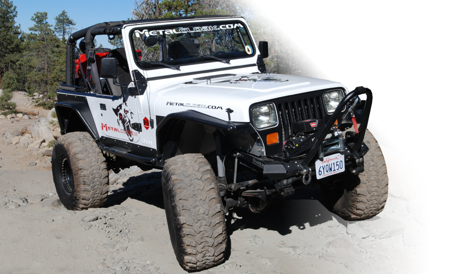 white Jeep YJ Wrangler driving over rocks