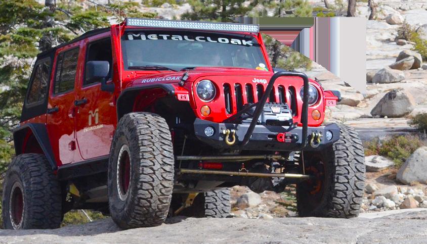 Red Jeep JK wrangler driving over rocks